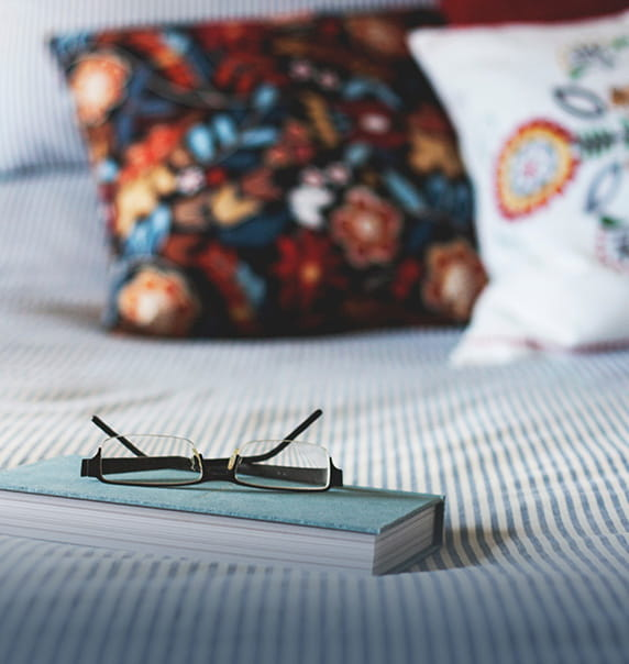 Notebook and glasses on a made bed.