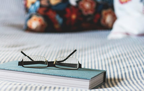 A notebook and glasses on a bed.