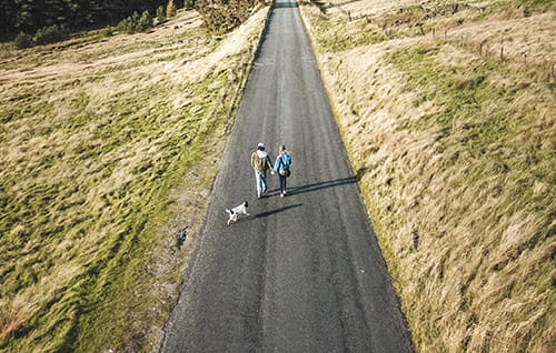 Couple walking down British country lane.